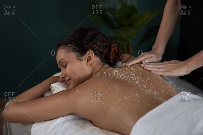 Woman enjoying a sugar sea salt natural body scrub exfoliation treatment with professional beautician