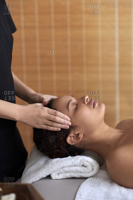 Beautiful mixed race woman getting head massage against bamboo background with lots of copy space