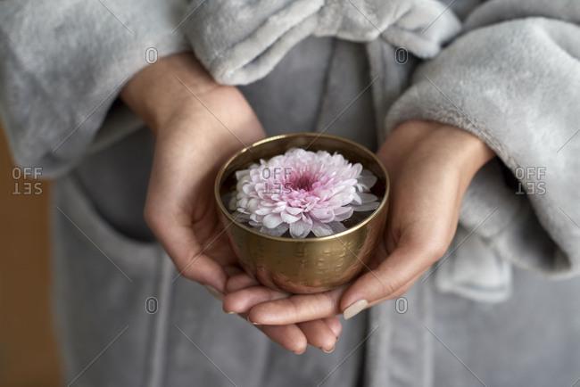 Hands holding elegant flower in metal bowl