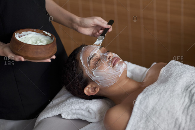 beauty therapist technician applying yoghurt face mask on client in day spa treatment room