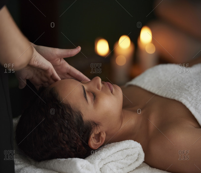 Woman in candle lit spa treatment room salon having a facial massage, calm zen peaceful pamper session