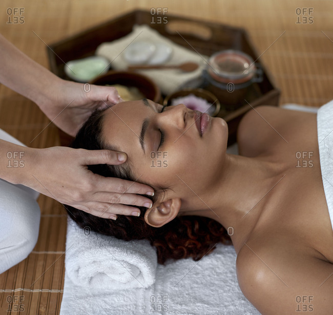 beautiful mixed race woman closing her eyes peaceful and relaxed during her head massage with professional therapist