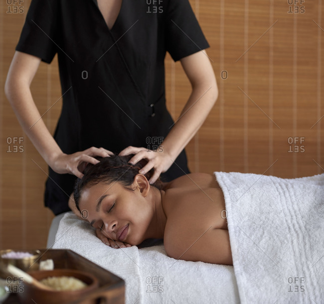 Professional massage therapist giving beautiful woman head massage in spa treatment room