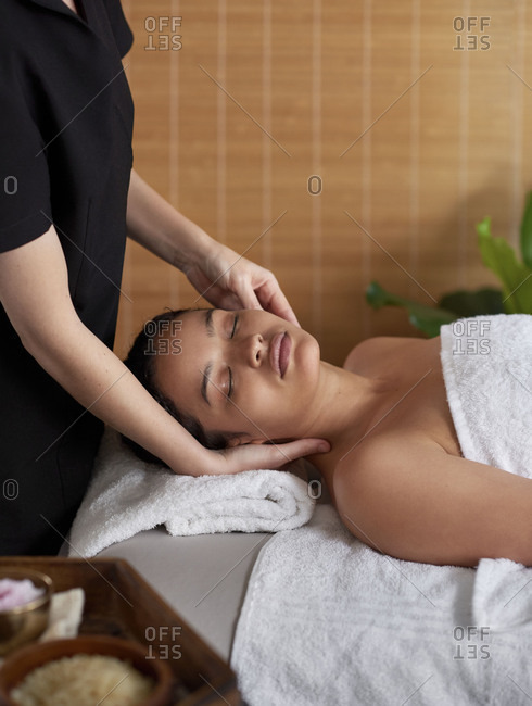 woman relaxing in spa treatment room, lying down enjoying head massage in natural room with bamboo blinds, copy space