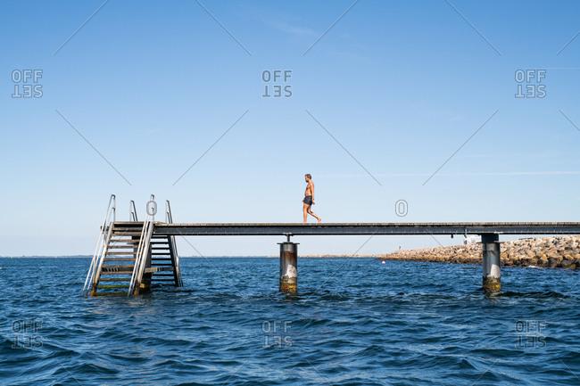 Man walking on ocean pier with steps