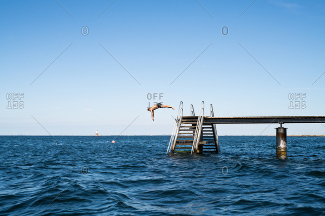 Man diving from ocean pier with steps