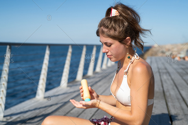 Woman in bathing suit putting on sunscreen by ocean