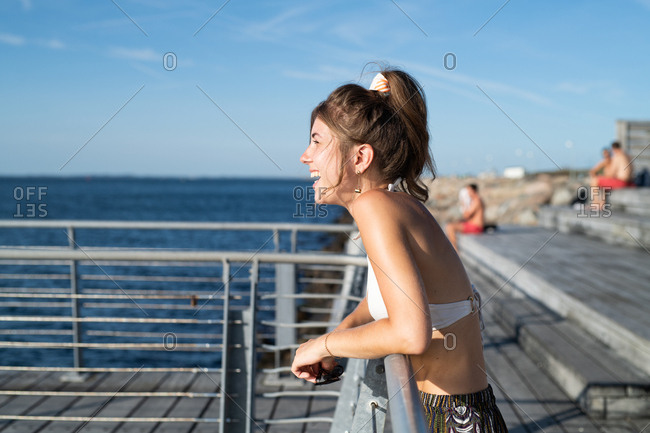 Woman in bathing suit leaning on pier railing by ocean laughing