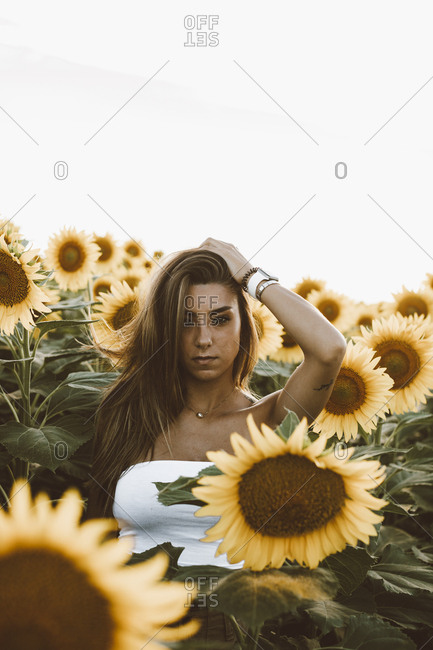 Portrait of a young woman standing in a field of sunflowers