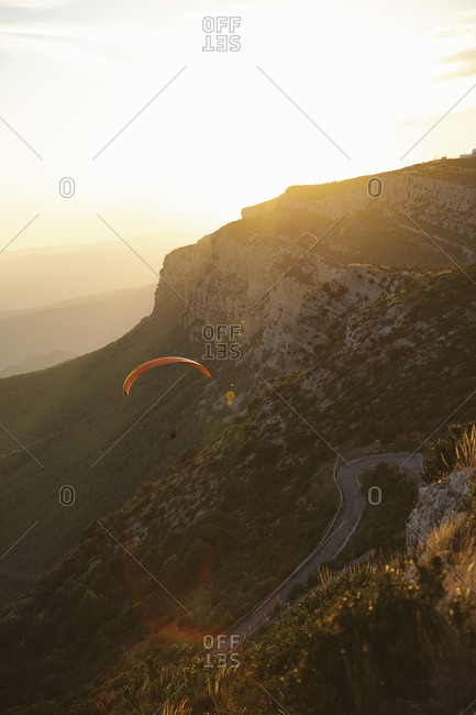 Paragliders soaring over mountain road on a sunny day