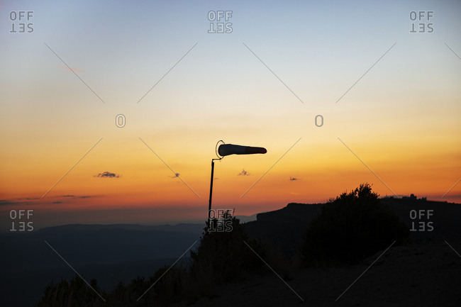 Silhouette of windsock at paragliding launch site at sunset