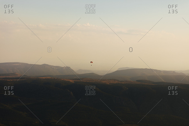 Paragliders soaring in the distance over scenic mountain area