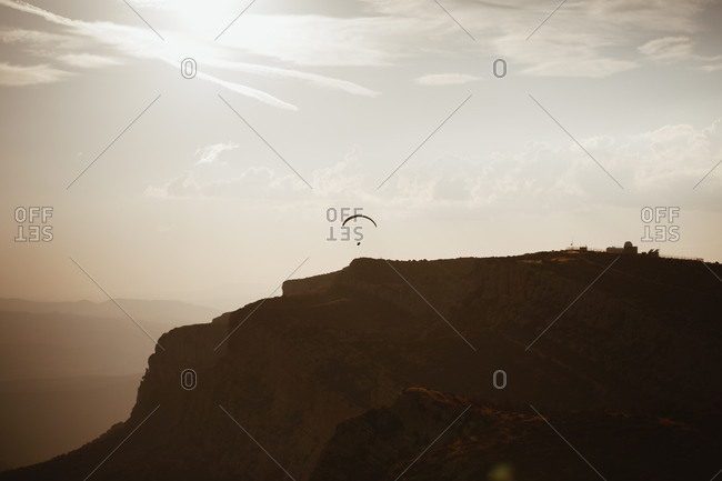 Silhouette of paraglider soaring in the distance above cliffs