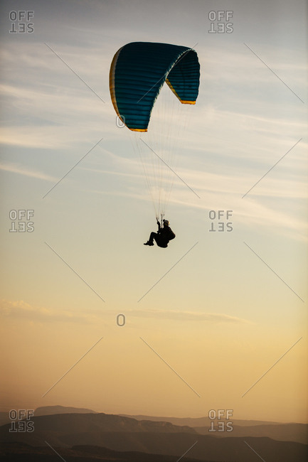 Silhouette of paraglider soaring high above the mountains at sunset