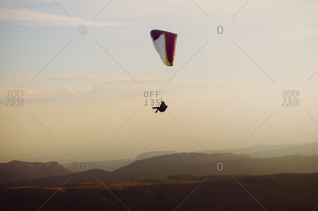 Paraglider flying high above the mountains at sunset