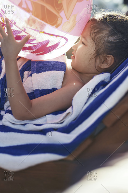 Exhausted girl with beach ball resting at the swimming pool