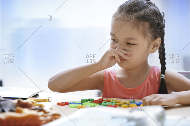 Girl wiping her nose while playing with toys