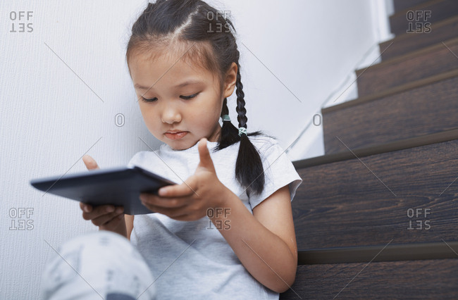 Cute 4-5 year old girl using tablet computer on stairs at home