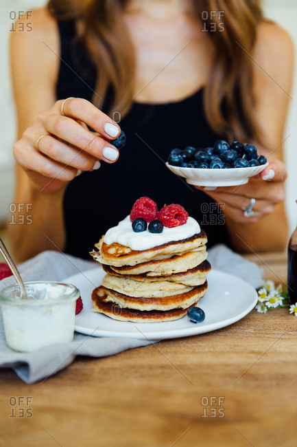 Woman adding blueberries to stack of pancakes