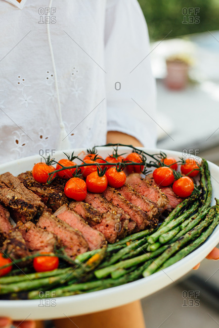 Sliced steak with asparagus and tomatoes