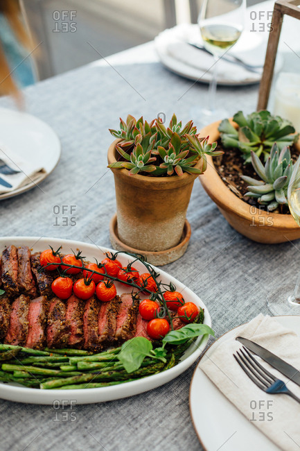 Sliced steak with asparagus and tomatoes on table