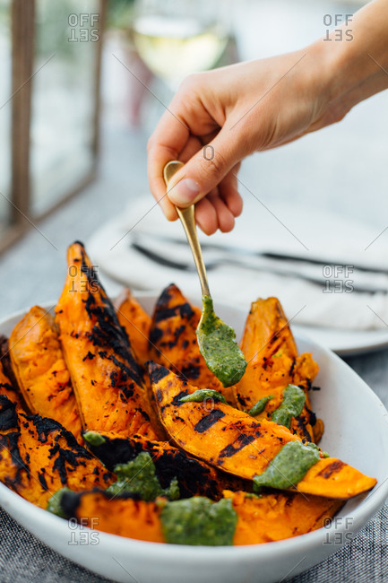 Woman adding chimichurri to grilled sweet potatoes