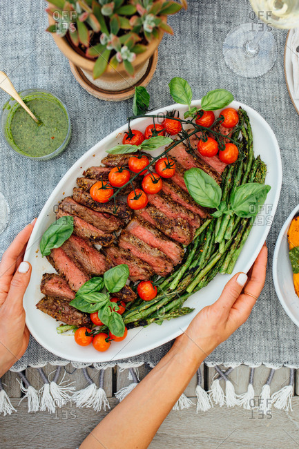 Woman holding plate with sliced steak with asparagus and tomatoes
