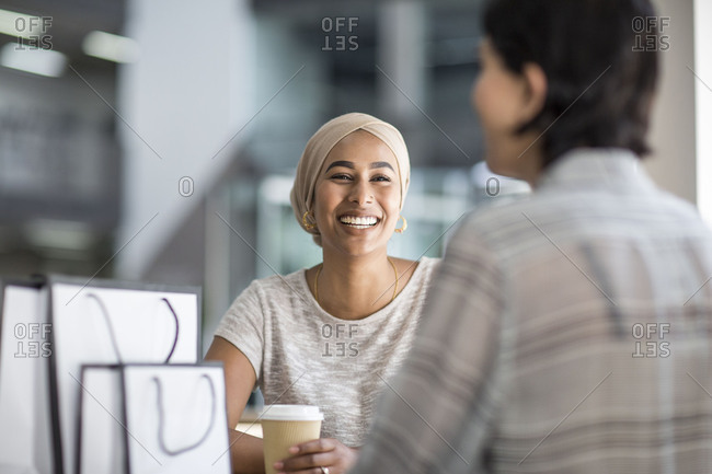 Female Muslim friends having coffee together in a shopping mall