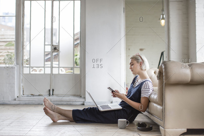 Millennial using smartphone and laptop in a loft apartment