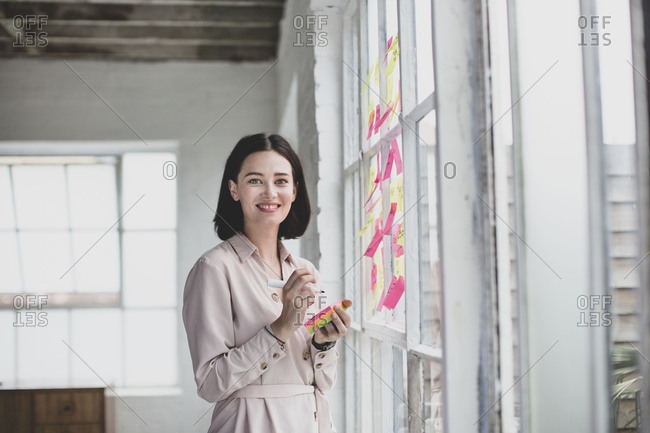 Portrait of young adult female brainstorming in a creative office with adhesive notes