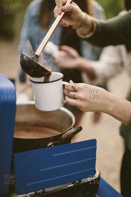 Woman pouring hot chocolate into a camping mug outdoors
