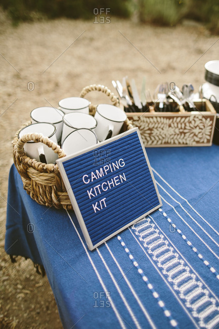 Stylized camping kitchen kit with enamel mugs