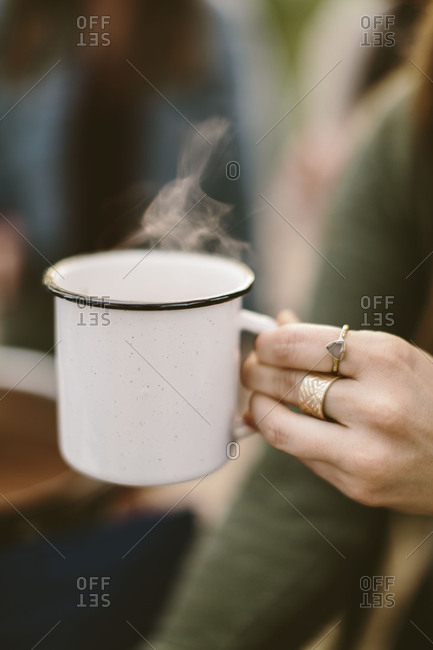 Woman holding a steaming mug of hot chocolate