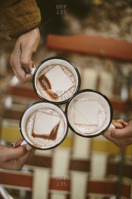 Overhead shot of people holding mugs of hot chocolate outdoors