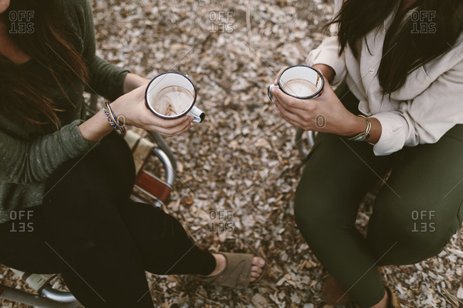 Overhead shot of women holding thier hot chocolate in camping chairs