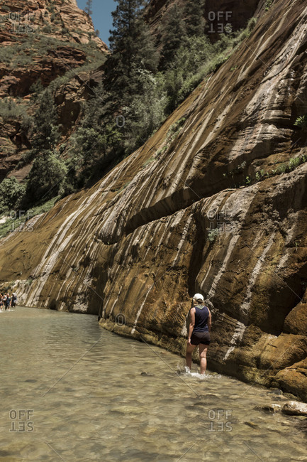 Woman hiking through the narrows Zion National Park