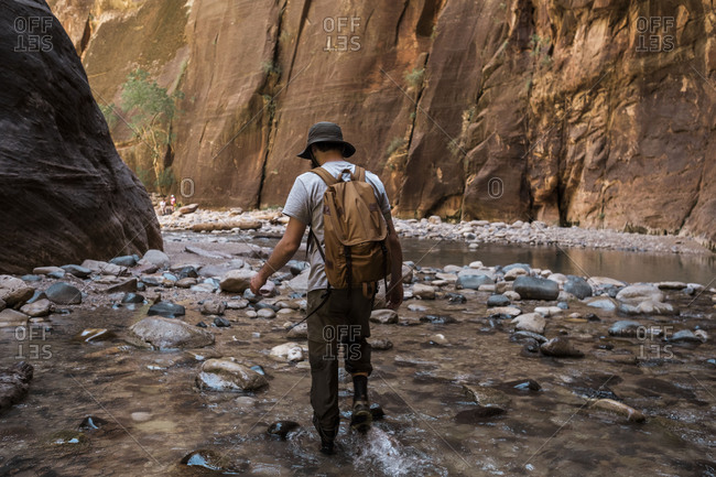 Man hiking through the narrows Zion National Park
