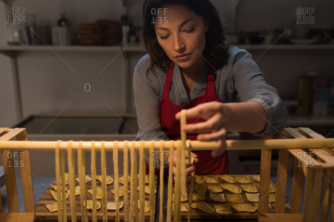 Beautiful female baker preparing pasta in bakery