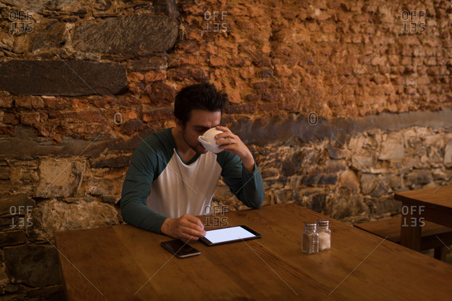 Businessperson having coffee while using a digital tab