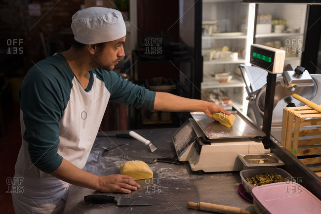 Male baker checking weight of dough in bakery
