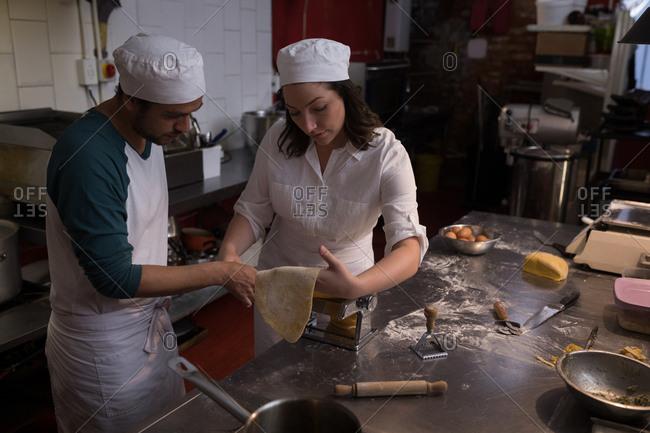 Bakers using machine for preparing pasta in bakery