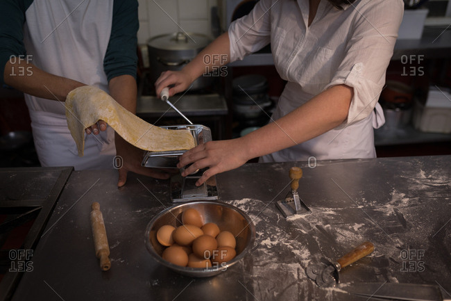 Mid section of bakers using machine for preparing pasta in bakery
