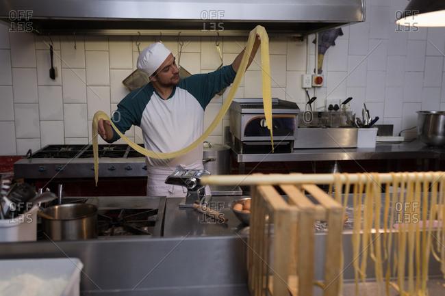 Male baker preparing pasta in bakery