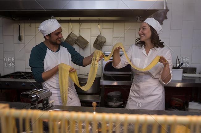Smiling bakers preparing pasta in bakery