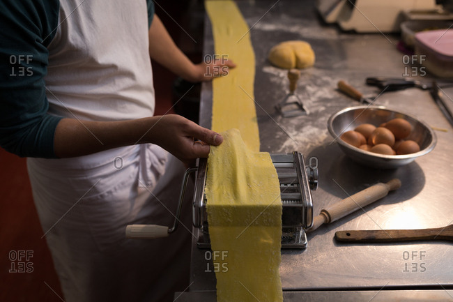 Close-up of baker using machine for preparing pasta in bakery