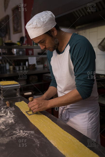 Male baker cutting pasta in bakery