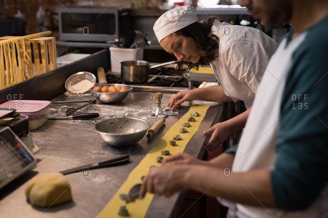 Attentive bakers preparing pasta in bakery