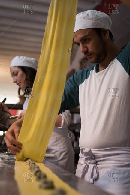 Close-up of bakers preparing pasta in bakery