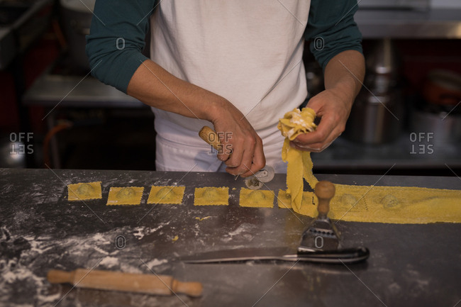 Mid section of male baker preparing pasta in bakery