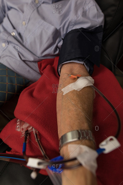 Mid section of senior man donating blood in blood bank